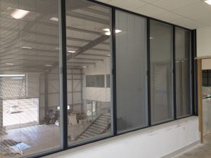 Interior shot of commerical building from the gallery through in integral blind into the main warehouse space